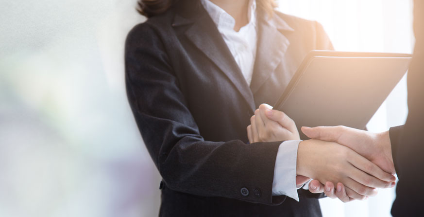 woman shaking hand while holding a portfolio